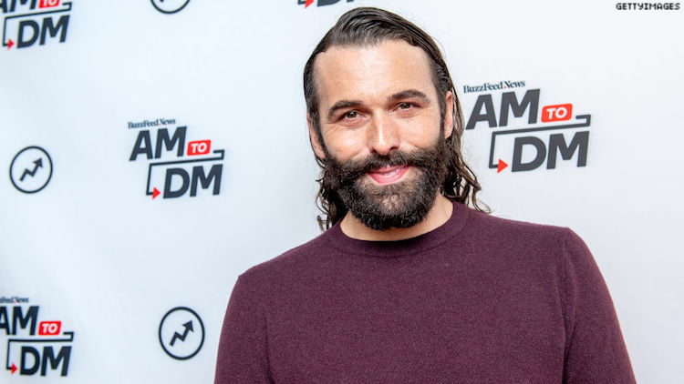 Jonathan Van Ness standing in front of a step and repeat, smiling.
