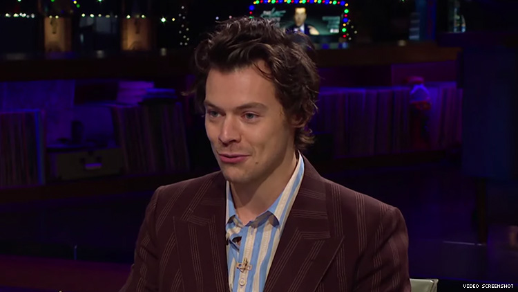Harry Styles in a suit sitting at a table.