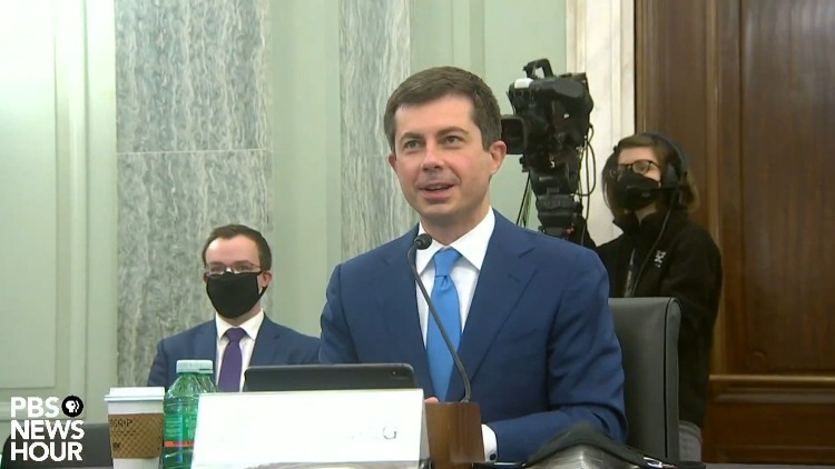 Pete Buttigieg introduced and thanked his husband, Chasten Buttigieg (in background), at his senate confirmation hearing considering his historic nomination for secretary of transportation.