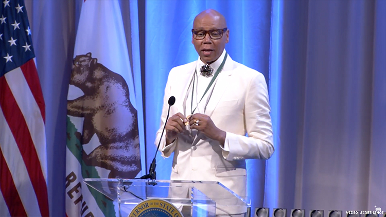 RuPaul on stage wearing an all white suit.