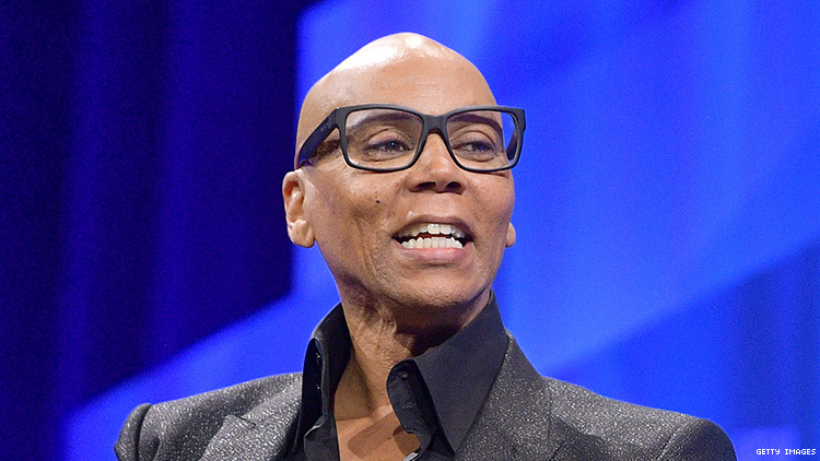 RuPaul, out of drag, laughing while giving a speech.