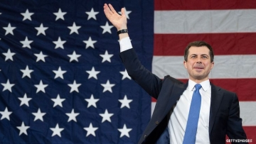 Pete Buttigieg in front of American flag