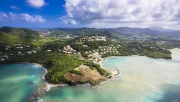 beautiful crescent shaped coastline next to rugged hill and populated Caribbean island