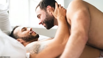 Two men in bed shirtless.