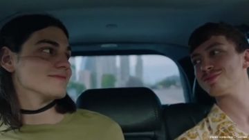 Two young gay boys sitting in the back of a car looking at one another.
