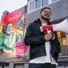 The artist Oz Montania at the mural unveiling outside of The Café in the Castro