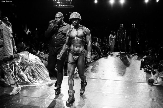 A shirtless man in army inspired gear on the runway.