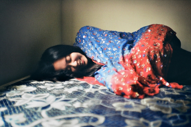 Woman laying in bed under a colorful blanket, smiling.