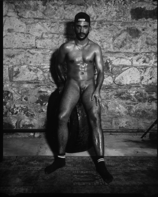 Billy Vega, a trans man, posing nude against a stone backdrop.