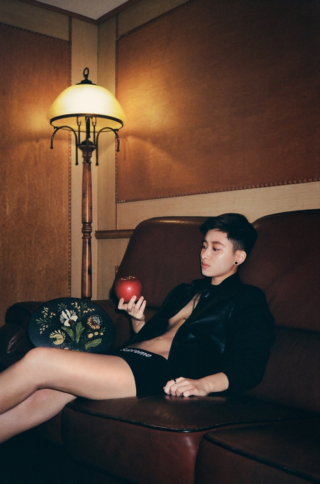 A person on a couch, shirtless but wearing a blazer.
