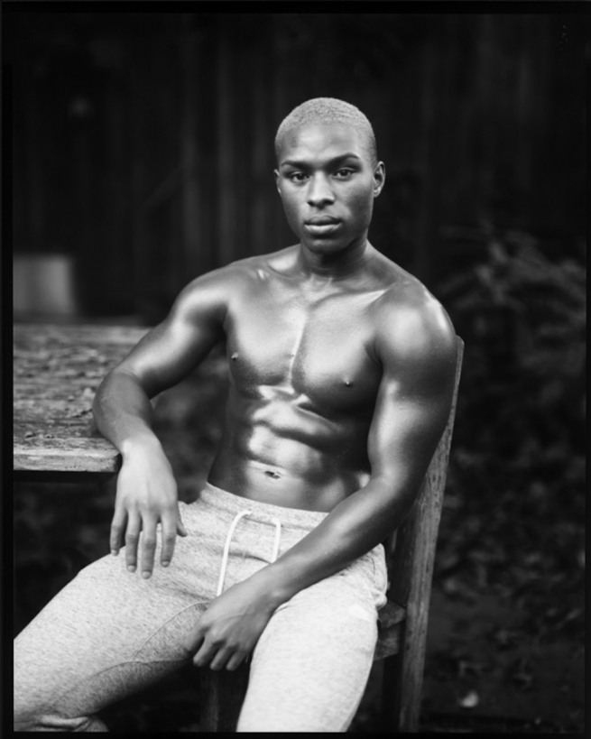 A model, sitting shirtless, with his chest oiled, looking at the camera.