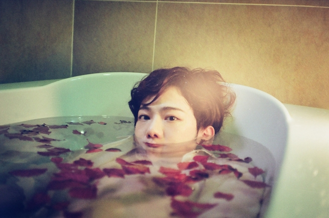 A person in a tub with their face half submerged in water. Flower petals float on the water.