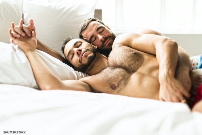 Two men shirtless in bed