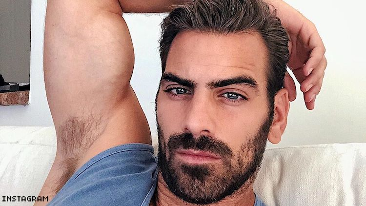 Nyle Dimarco reclining on his couch.