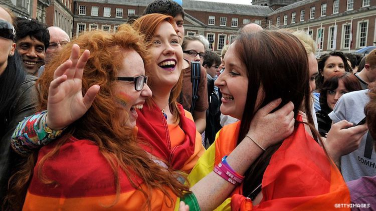 Two women about to kiss at a protest.
