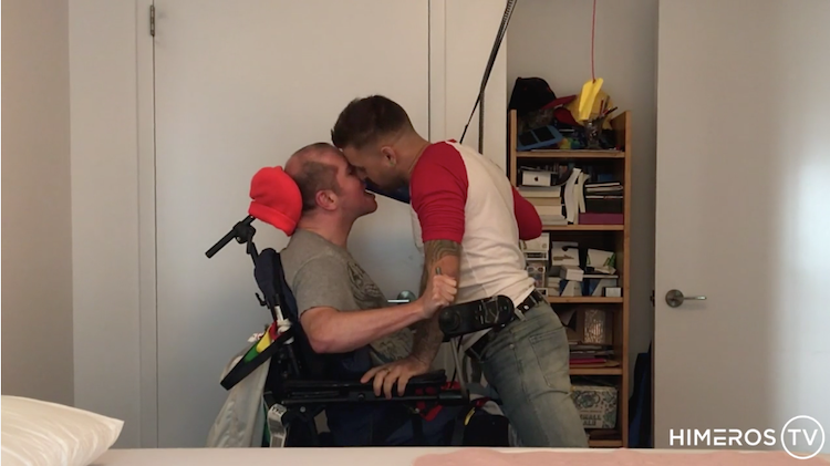 Two porn performers, one in a wheelchair, kissing.