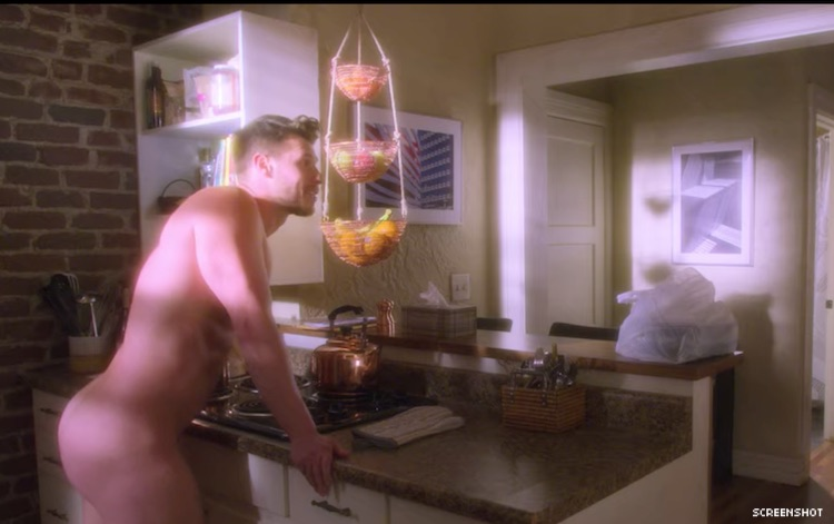 A shot from AJ and the Queen with a guy standing in a kitchen with no pants on.