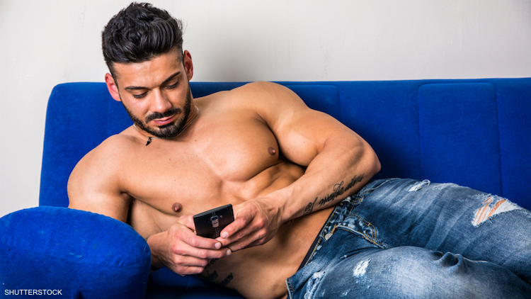 Shirtless man texting on his phone.