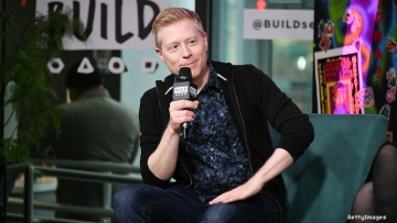 Actor Anthony Rapp on stage with a mic smiling.