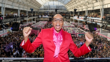 RuPaul at Drag Con UK on a balcony above thousands of dancers.