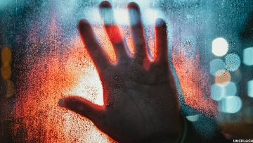 Stock photo of a hand against a window.
