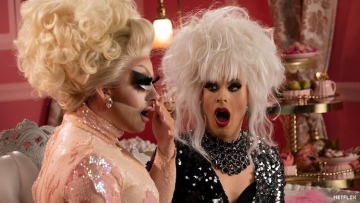 Trixie and Katya in drag sitting on a couch looking surprised.