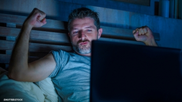 Guy watching computer screen while in the dark.