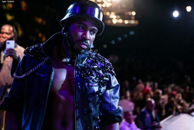 Shirtless man in a bejeweled leather jacket.
