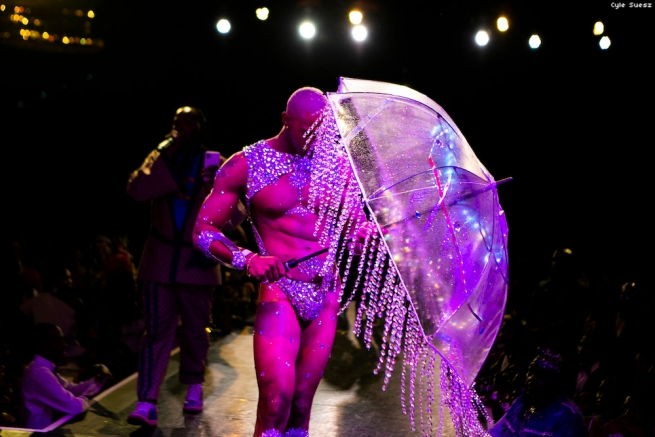 Man in a bejeweled thong emerging from under a clear umbrella dripping with crystals.