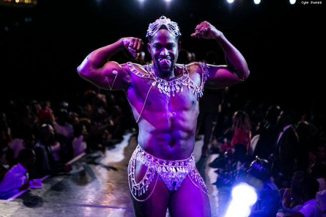 Muscular man flexing in a thong with crystals and charms on it.