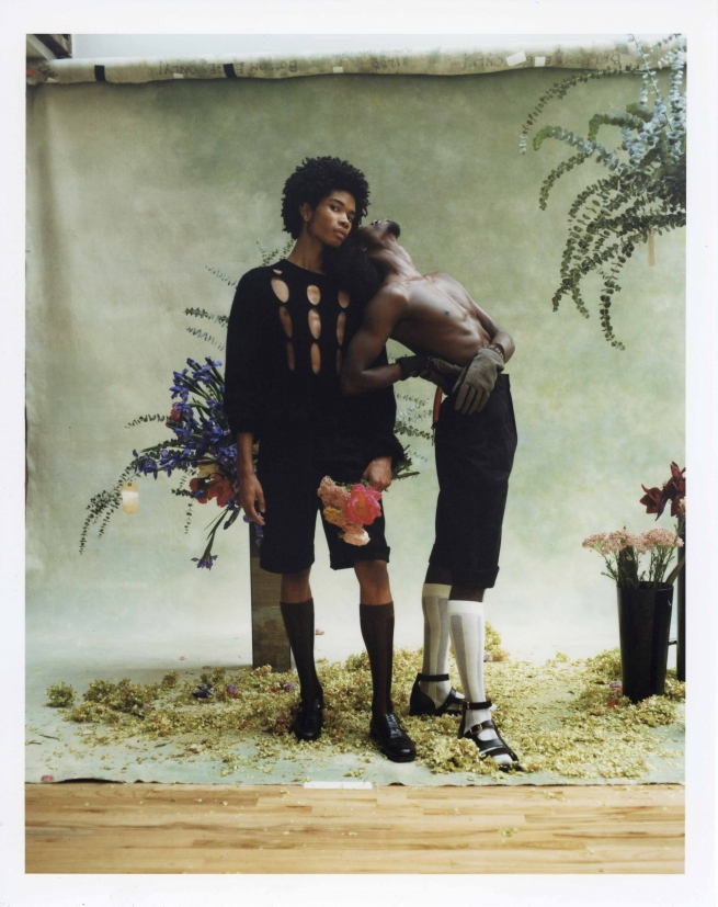 Two models dressed in Fendi holding flowers.