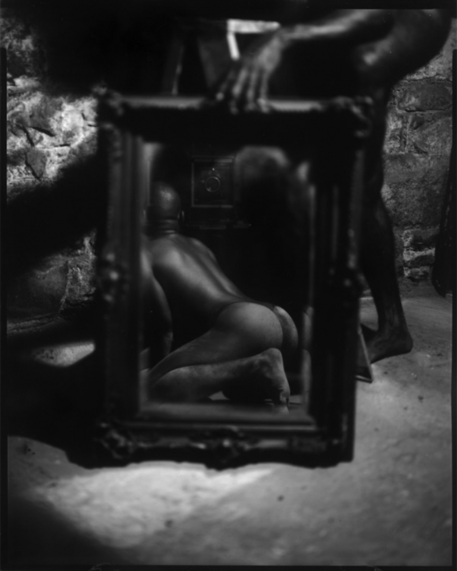 An anonymous man's reflection, as he kneels on the floor, from behind.
