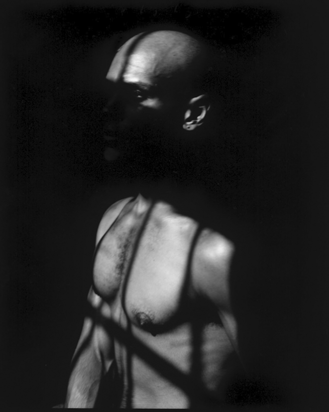 A shirtless man obscured in the shadows of a window.