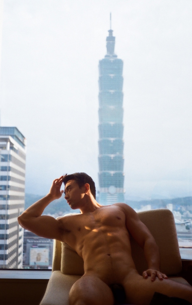 A man reclining nude infant of his window with a skyscraper in the background.