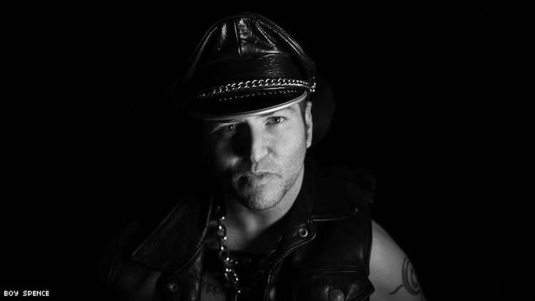 Andrew Gurza in a leatherman's cap and motorcycle jacket.